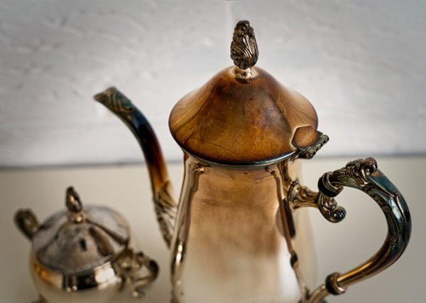 a tarnished antique tea set on a table