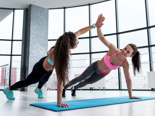 two women doing a high-five while working out together