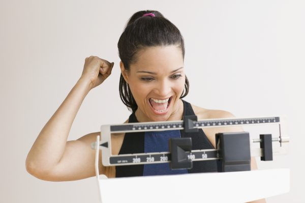 a hispanic woman cheering on the success of her weight loss on a scale