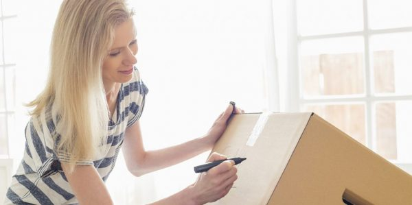 a woman writing on a cardboard box for moving