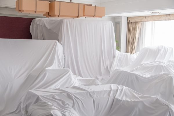 white dust cover cloth covering furniture in a room