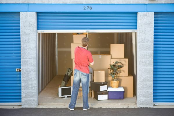 a man shutting the gate of his storage unit down