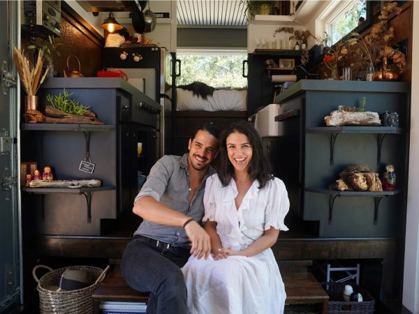 a happy couple sitting in their tiny house