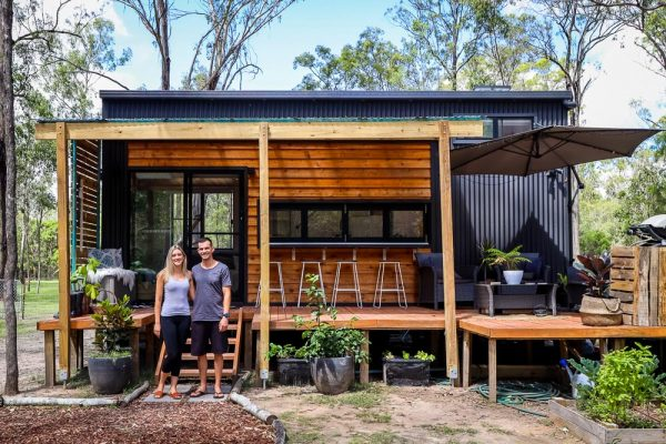 a couple standing outside of their tiny house