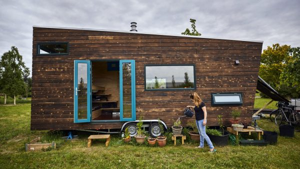 a woman watering plants outside her tiny home