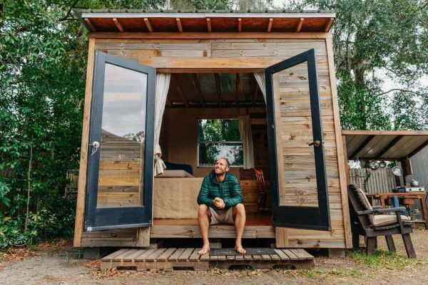 a man sitting on the edge of his tiny house while looking up