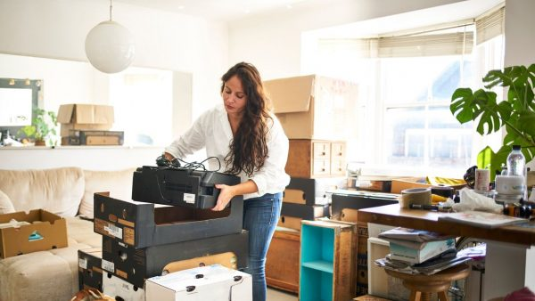 A woman placing a printer inside a cardboard box
