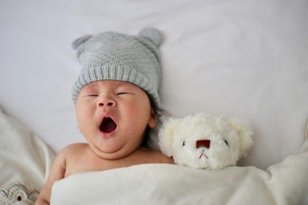 A baby yawning beside a teddy bear