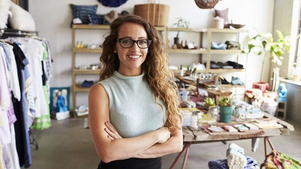 A business woman smiling with her arms crossed in her shop
