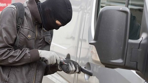 A bulglar breaking into a van