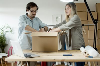 A couple packaging a box