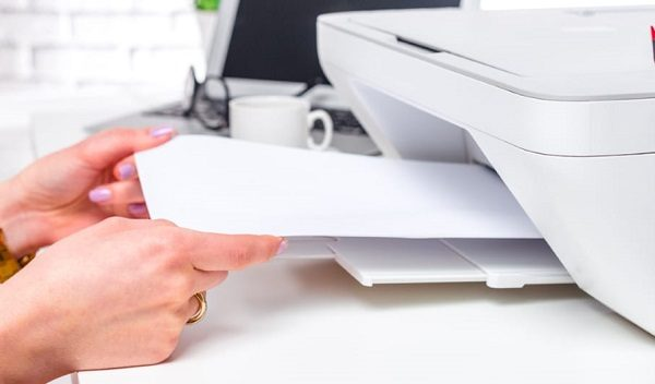 A woman sticking paper in a printer